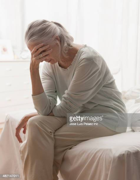 Senior Caucasian woman holding head in hand on bed