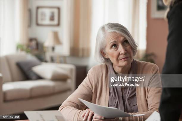 Senior Caucasian woman holding papers at desk