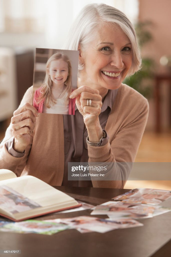 Senior Caucasian woman holding photograph of young girl
