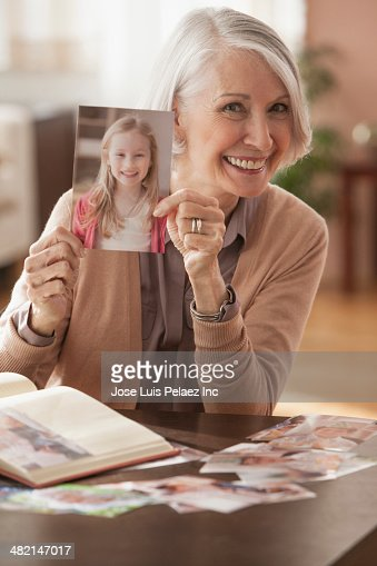 senior caucasian woman holding photograph of young girl photo getty images. Black Bedroom Furniture Sets. Home Design Ideas