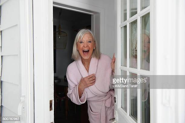 Senior Caucasian woman opening door in bathrobe