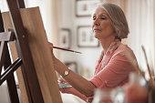Senior Caucasian woman painting at easel