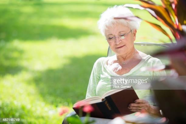 Senior Caucasian woman reading book outdoors