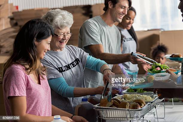 Senior Caucasian woman serves meal in soup kitchen