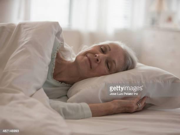 Senior Caucasian woman sleeping in bed