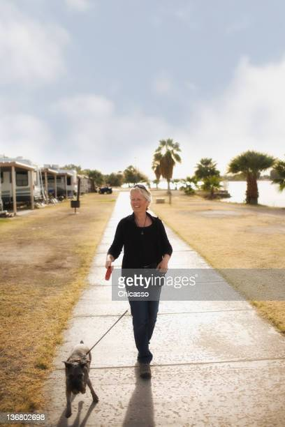 Senior Caucasian woman walking dog on sidewalk