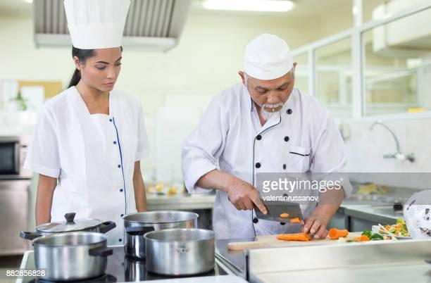 Senior chef preparing asian food in restaurant's kitchen