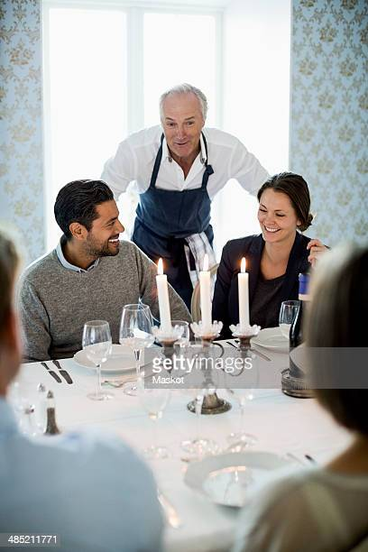 Senior chef talking to business people at dining table in restaurant