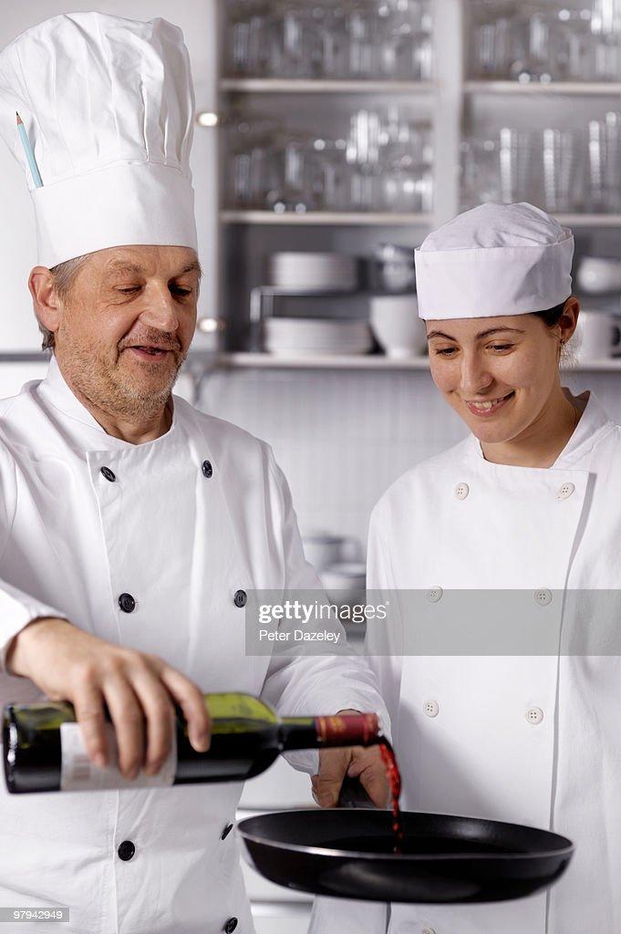 Senior chef teaching trainee to flambe in kitchen : Stock Photo