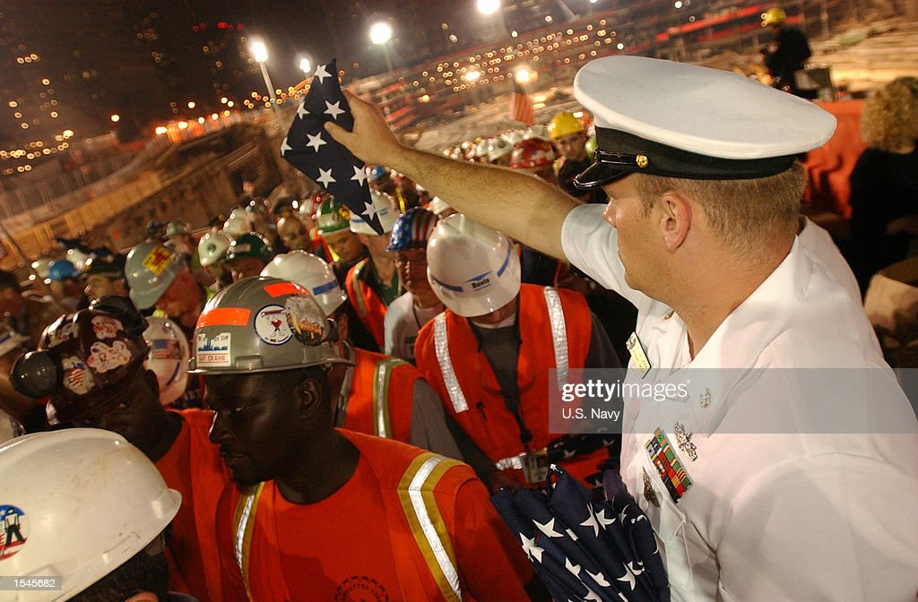 Senior Chief Operations Specialist Tim Easter of Afloat Training Group, Mayport, FL, and over 500 Sailors from 20 U.S. Navy ships in New York City for the 15th annual Fleet Week celebration, turned out to render honors and present flags to workers at 'Ground Zero' May 28, 2002 following the removal of the last remaining World Trade Center structure, Column Number 1001B of Two World Trade Center. The 30-foot column remained standing following the collapse of the twin towers, when terrorists flew two commercial airliners into both skyscrapers on September 11, 2001. The resulting collapse created a mountain of 1.8 million tons of steel and concrete. More than 3000 people perished in the attack.