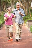 Senior Chinese Couple Jogging In Park Towards Camera