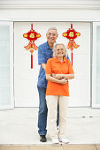 Senior Chinese Couple Outside Home Decorated With Welcoming Feng Shui Banners