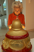 Senior Chinese Woman Praying To Statue Of Buddha At Home