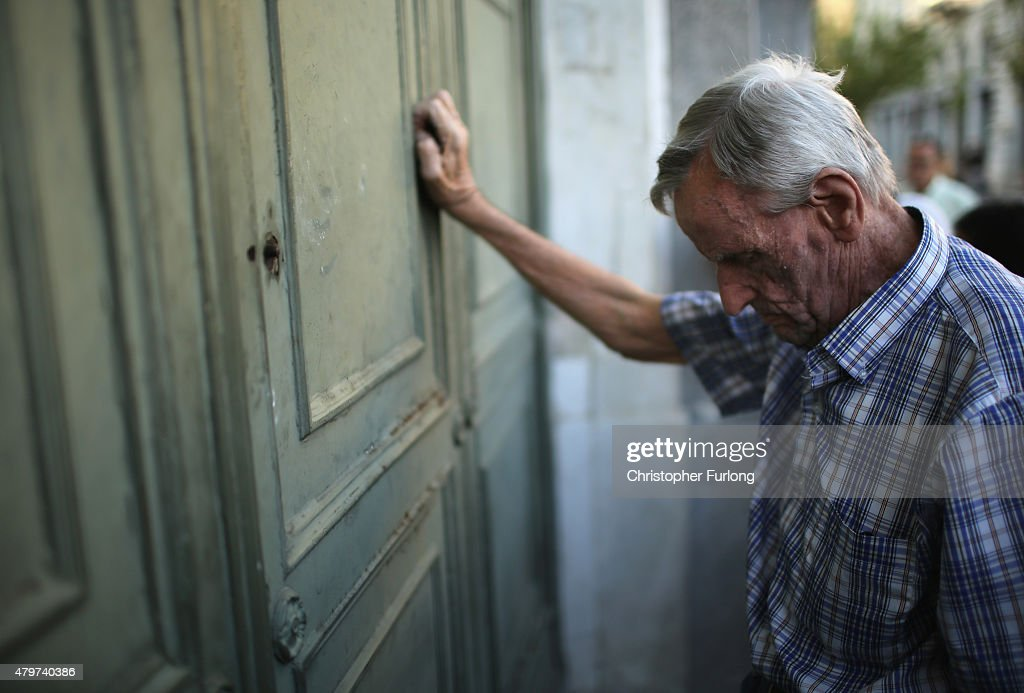 A senior citizen leans against the door of a closed bank as he queues up to collect his pension outside a National Bank of Greece branch in Kotzia...