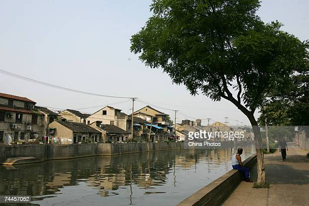 A senior citizen sits on a shore of the ancient Jinghang Canal on June 8 2007 in Wuxi of Jiangsu Province China June 8 2007 in Wuxi of Jiangsu...