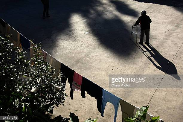 A senior citizen takes a walk in the yard of the Happy Times Nursing Home on December 12 2007 in Kunming of Yunnan Province China Twothirds of the...