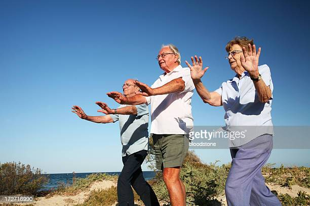 Senior citizens doing Tai Chi at seaside