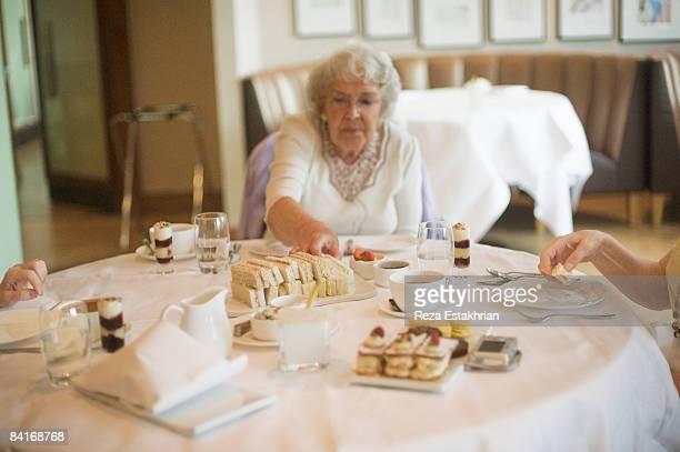 Senior citizens enjoy high tea in a restaurant