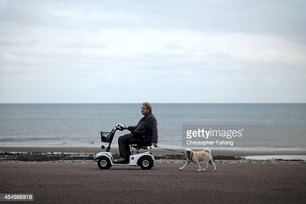 A senior citizens enjoys the sea air on Llandudno Promenade on September 8 2014 in Llandudno Wales Britain is facing multiple problems stemming from...