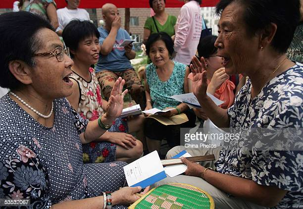 Senior citizens learn English words at a residential area during a community activity in Haidian District on August 29 2005 in Beijing China The...