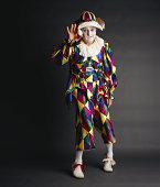 Senior clown holding egg, portrait