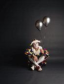 Senior clown holding silver ballons