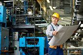 Portrait of senior man holding plans and looking away in workshop of modern factory
