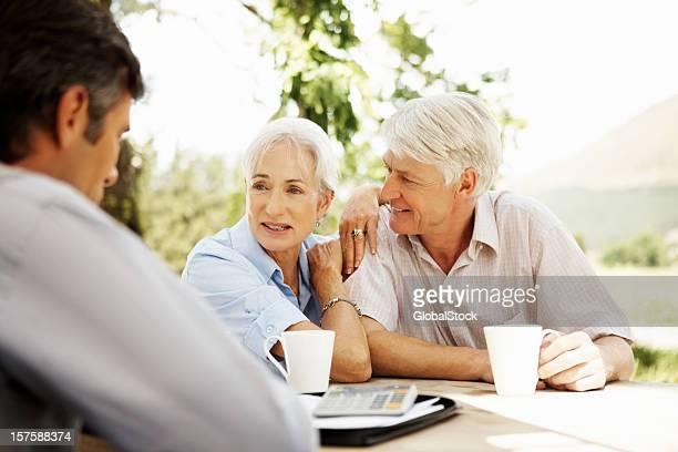 Pareja Senior y hombre de negocios sentado en una mesa al aire libre