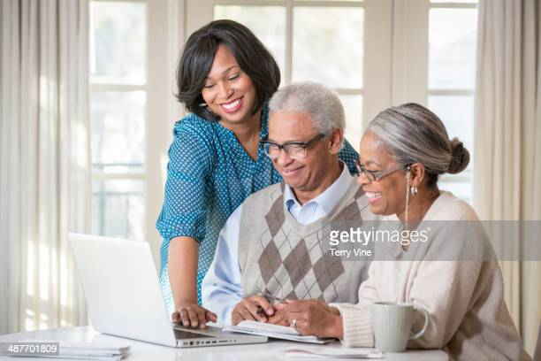 Senior couple and daughter using laptop together