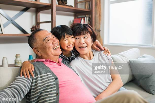 Senior couple and granddaughter hugging