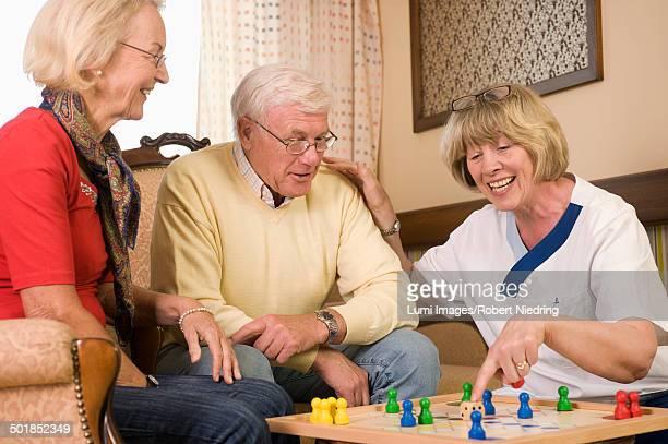 Senior couple and nurse playing ludo together, Bavaria, Germany