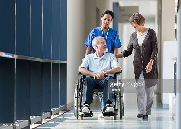 Casal Idoso e enfermeira A andar de um corredor de Hospital