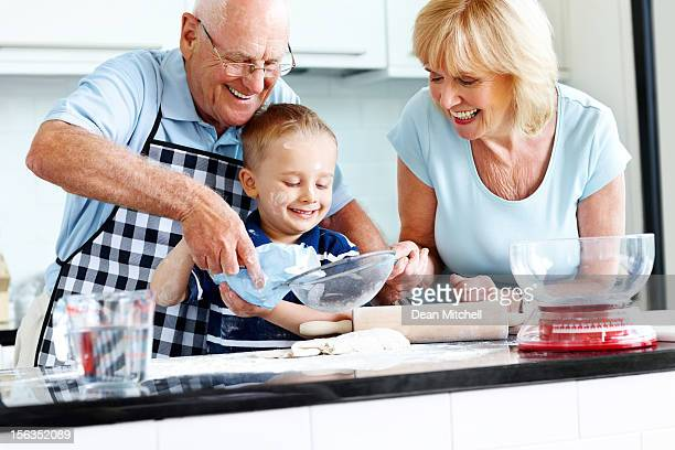 Senior couple and small kid preparing food