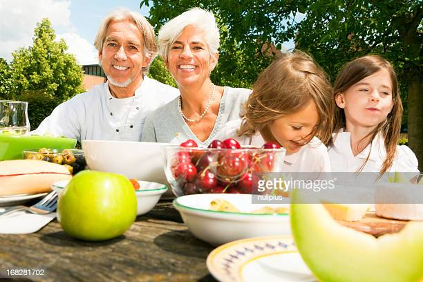 senior couple and their grandchildren are having a picnic