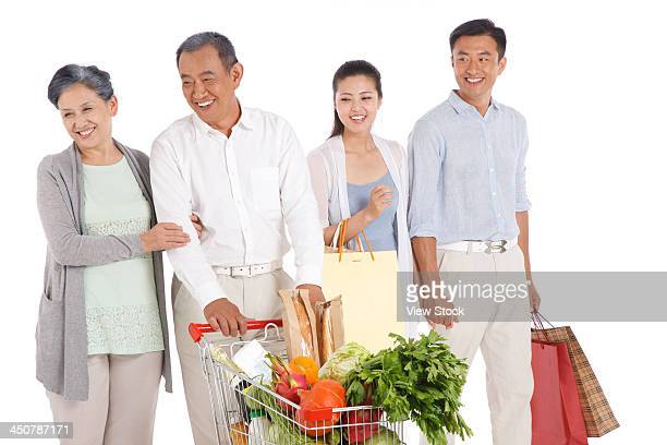 Senior couple and young couple shopping with shopping cart