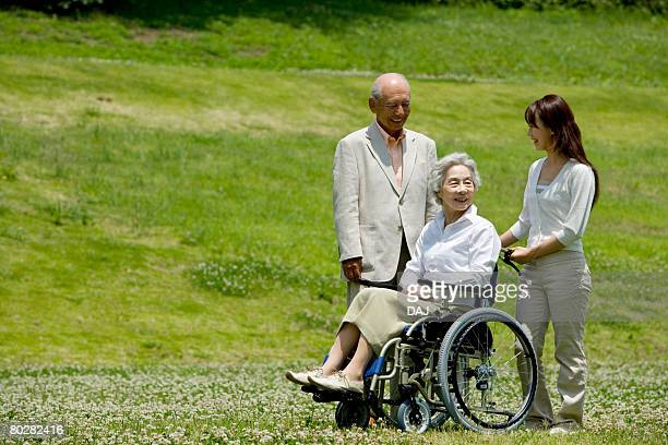 Senior couple and young woman in the field, young woman pushing senior woman in wheelchair