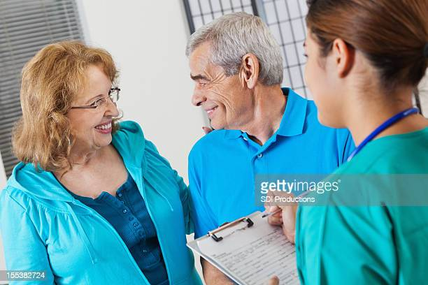 Senior couple answering questions as nurse fills out patient form