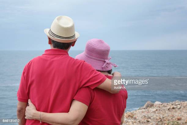 Senior couple arm in arm enjoying adriatic seascape.