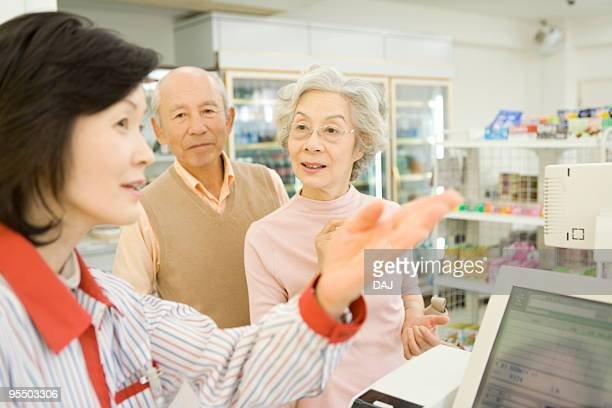 Senior couple asking cashier for direction