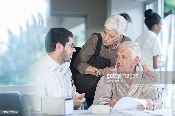 Senior couple at clinic talking to doctor