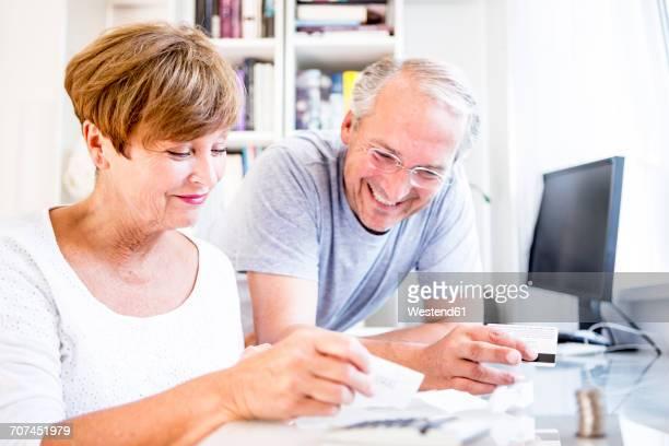 Senior couple at desk paying bills