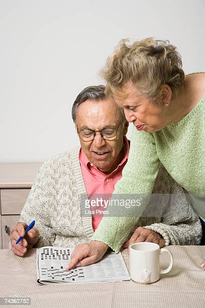 Senior couple at home doing crossword puzzle