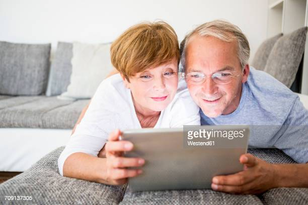Senior couple at home lying on couch using digital tablet