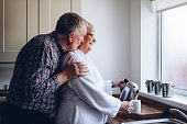 Senior man kissing his wife from behind as she pours a cup of tea.