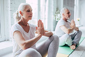 Senior couple is doing fitness training at home. Doing yoga together. Healthy lifestyle concept.