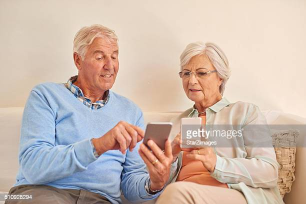 Senior couple at home together using smartphones