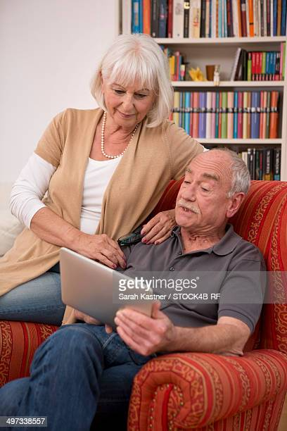 Senior couple at home using laptop