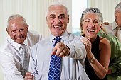 Senior couple at party pointing in surprise