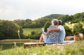 Beautiful senior couple at the lake having a picnic. Green sunny summer nature.