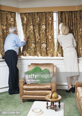 Senior couple at window, peering around curtains, rear view